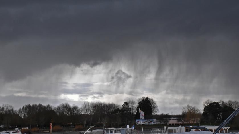 kein schwarz-weiss Bild! Regenschauer, schauriger Regen fällt aus düsteren Wolken