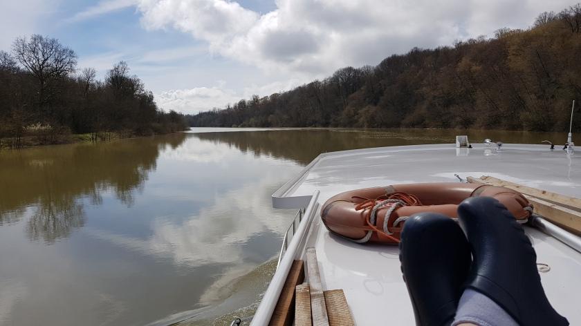 Blick von mir über meine Clogs hinweg auf Deck und Fluss, glattes Wasser, fast windstill