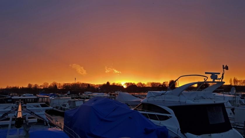 Blicküber die Boote hinweg auf die schön fast untergegangene Sonne. Der Himmel leuchtet in tiefen Violett-, Lila- und Gelbtönen