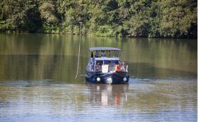 Ankommendes Boot vor einer Schleuse die mittels hellblauer Stange (links vom Boot) bedient wird