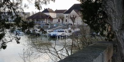 Blick auf die Anlegestelle unter den Bäumen hindurch. Man sieht links die Capitainerie mit den Booten und dahinter die Kirche