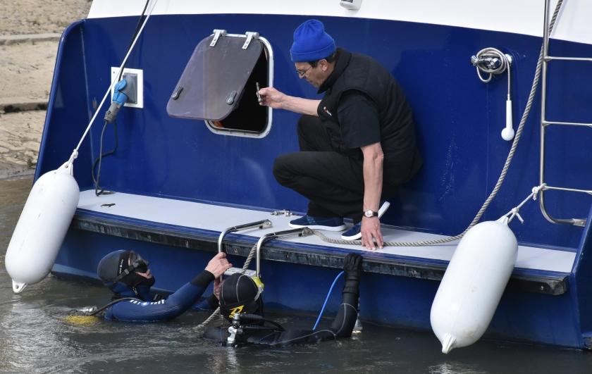 Auch an anderen Booten wird gearbeitet - sogar unter Wasser. Taucher flicken das Ruder
