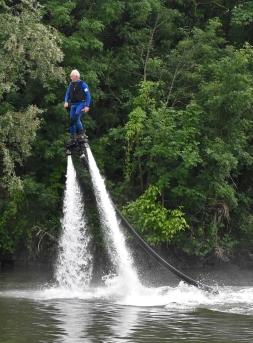 Fly Board - Man, Mann auf Wasserstrahl stehend