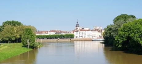 Blick vom Hafen über die Saône hinweg auf den grösseren Stadtteil mit Quaimauer und -Stufen und die historischen Gebäude