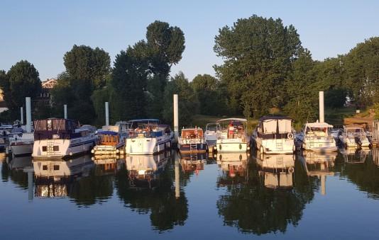 Einige Boote im Hafen werden durch die letzten Sonnenstrahlen beleuchtet und erstrahlen in warmen Farben