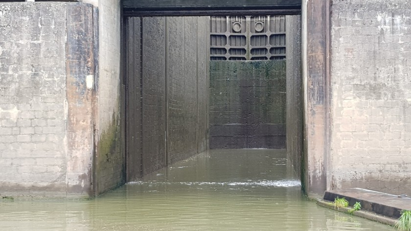 Die Schleuse ist bereit für uns. Das Guillotine-Tor offen, hinter dem Schleusenbereich sieht man die gegenüberliegende Mauer und darüber das Tor, durch das wir in Kürze wieder hinausfahren werden