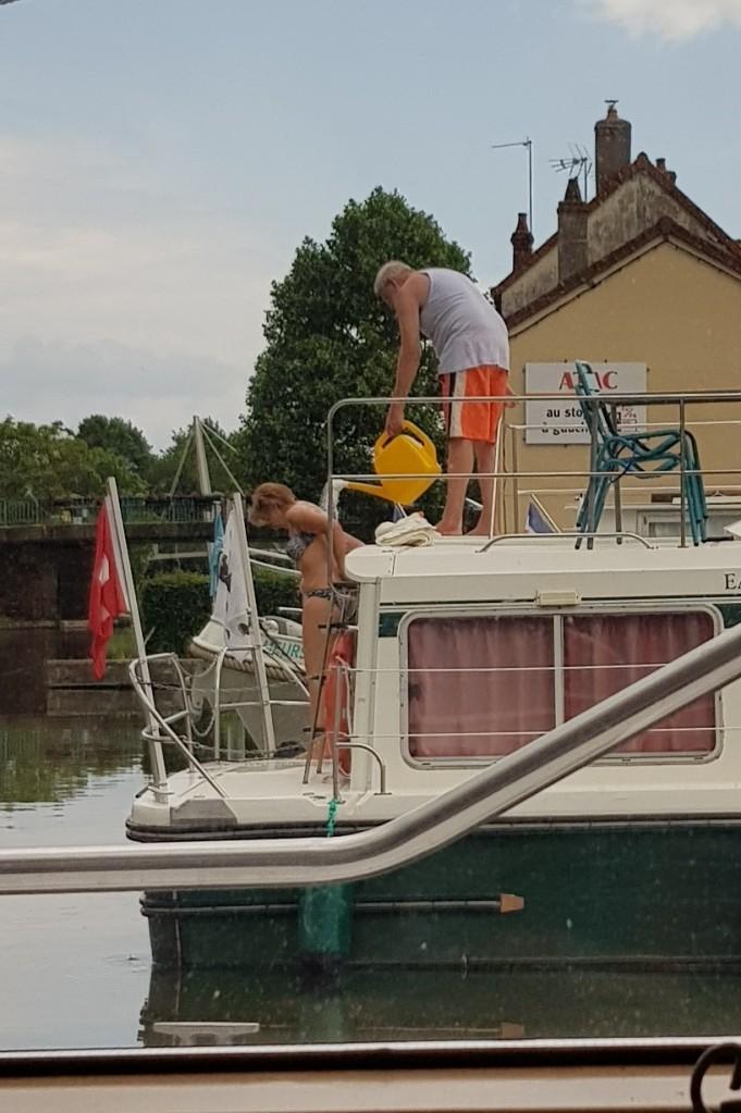 Unsere Nachbarn beim Freiluftduschen an Bord. Die Seife wird mittels Giesskanne abgewaschen