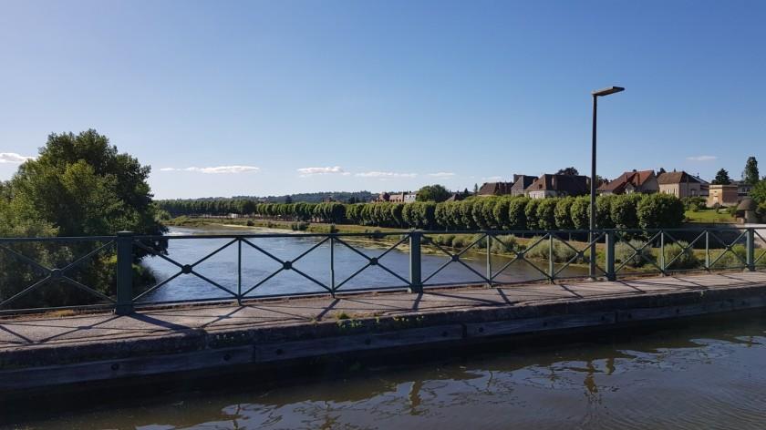 Von der Kanalbrücke auf die Uferpromenade und die Stadt blickend