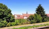 Dachlandschaft hinter Bäumen. Für uns namenloses, typische Dorf am Kanal mit Treidelpfad im Vordergrund