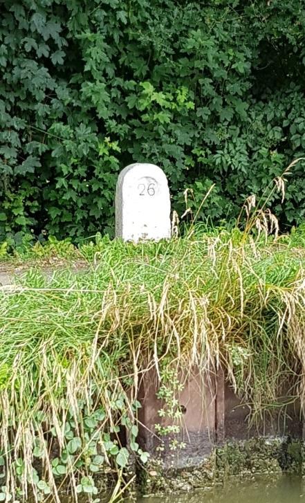 """Uralte, steinerne Wegmarke am Kanal. Die Angabe darauf bezieht sich möglicherweise auf ein altes französisches Wegmass, das """"lieu"""""""