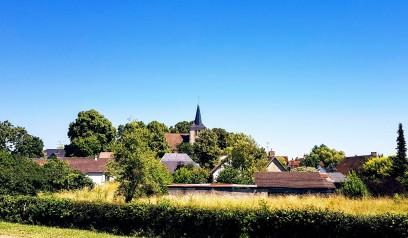 Man sieht nur die verschiedenen Dächer über dem Grün. Hübsches Dorf am Kanal