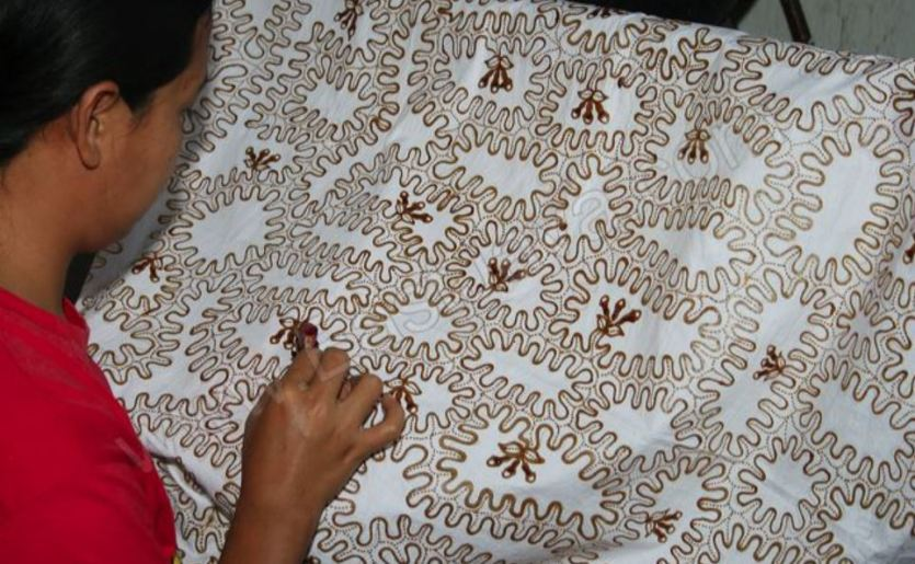 Batik tulis - der heisse Wachs wird mit einem Minikännchen aufgetragen. Alles, was keine Farbe annehmen soll, wird so abgedeckt. Für ein buntes Muster braucht es viele solcher Durchgänge