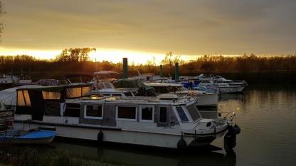 Der Steg und die Boote liegen bereits im Halbdunkel, dahinter ist der Himmel noch hell