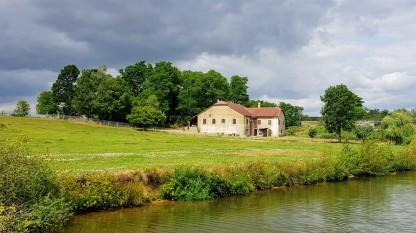 eine stattliche 'ferme' (Bauernhaus) vor gewittrigem Himmel