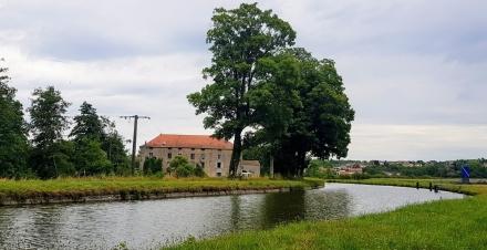 Die riesige, alte Mühle von Ormoy liegt zwischen Kanal und Fluss