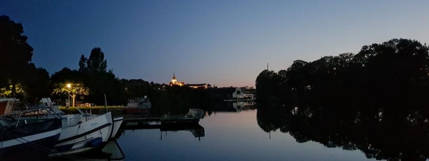 Liegeplatz nach Sonnenuntergang mit der beleuchteten Kirche von Gray in der Ferne