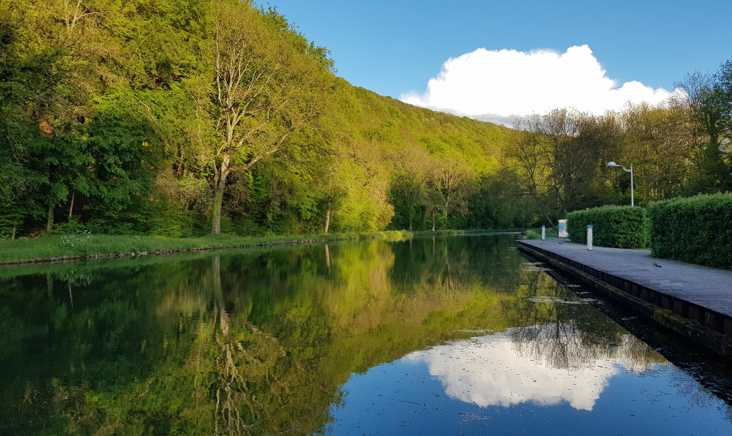 Erster Abend in Froncles. Der Kanal ist glatt wie ein Spiegel und der blaue Himmel, eine grosse weisse Wolke und der nahe Wald spiegeln sich darin