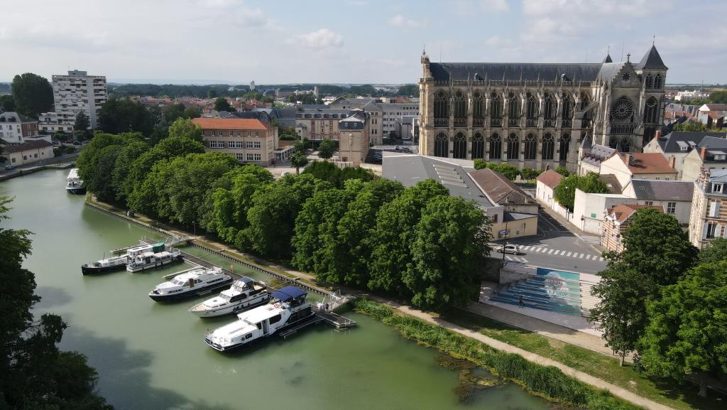 Im Vordergrund sieht man die Anlegestelle mit Kai und Schwimmsteg, dahinter eine Zeile Kastanienbäume und Teile der Stadt mit der dominanten, alles überragenden, gotischen Kathedrale
