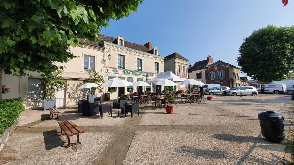 Der Dorfplatz in Hautevillers mit Restaurantterrasse im Morgenlicht