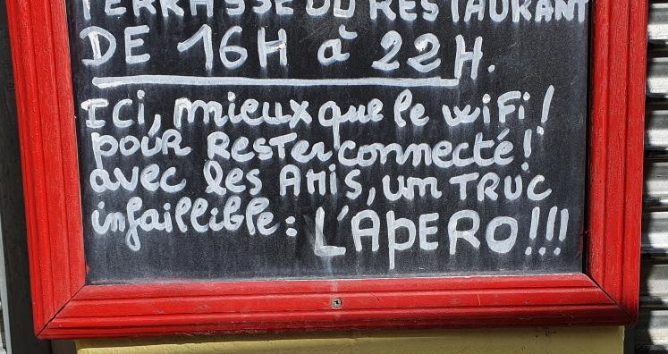 Ein mit Kreide auf eine Tafel geschriebener Text vor einem Restaurant: