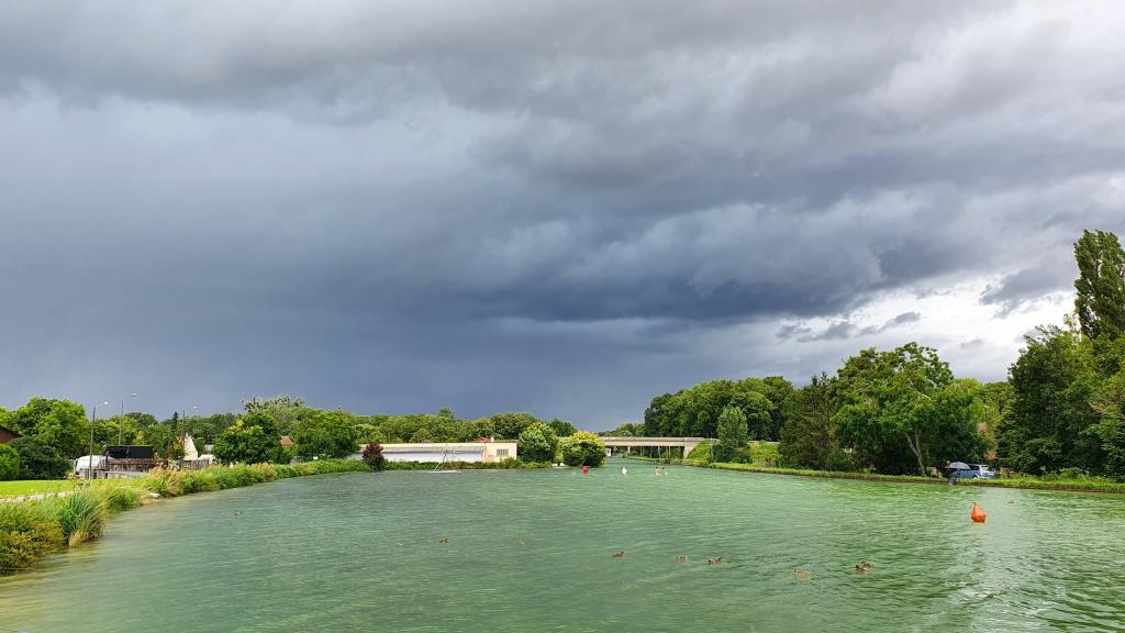 Ein Gewitter zieht auf, shellgrünes Wasser vor dunkelgrauem Himmel